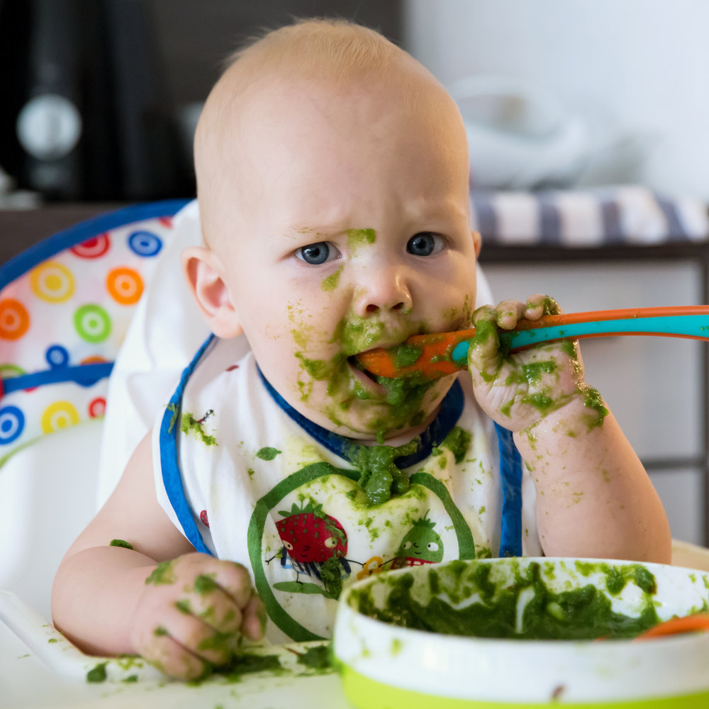 """A good rule of thumb is to watch your baby and not the calendar. Some signs that your baby might be ready for solids...  Able to sit with support  Reaches and grabs, and mouths hands and toys  Baby can show and tell. Around six months of age babies have the ability to say """"yes"""" to wanting food by reaching or leaning toward the food and """"no"""" by pushing or turning away. Expect mixed messages as your baby learns to communicate. Offer, but don't force.  For more information on feeding your baby solids:  https://www.askdrsears.com"""
