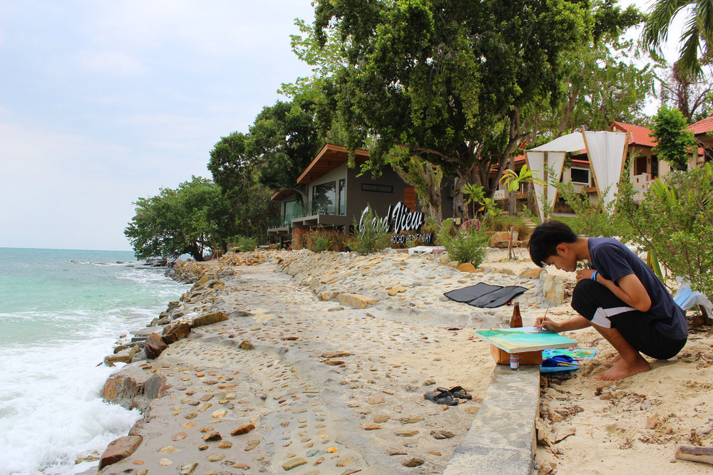 Thai hipsters painting by the ocean.