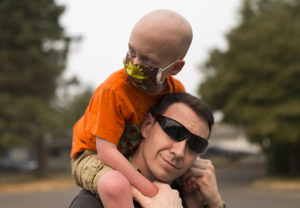 "Declan Reagan, 5, sits atop of Francis' shoulders outside the Washougal Police Department where his dad works in Washougal on Tuesday, Sept. 5, 2017. Declan's leukemia relapsed earlier this year and he was also diagnosed with lymphoma. A recent bone marrow transplant has him on his feet again and back to his up-beat self. ""A woman in another country gave him the chance to have a life, and that's really cool"" says his mother, Lauren. (The Columbian)"