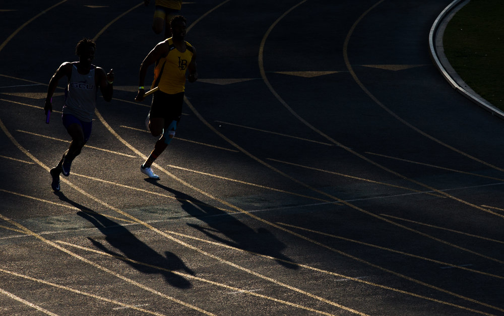Grand Canyon University's Marcus Flanagan, left, and Long Beach State Community College's Kemonie Briggs race alongside each other in the 4x400 men's relay at University of California, Irvine in Costa Mesa, CA, on Saturday, April 28, 2018. Grand Canyon University won by 0.1 seconds, beating out Long Beach State.