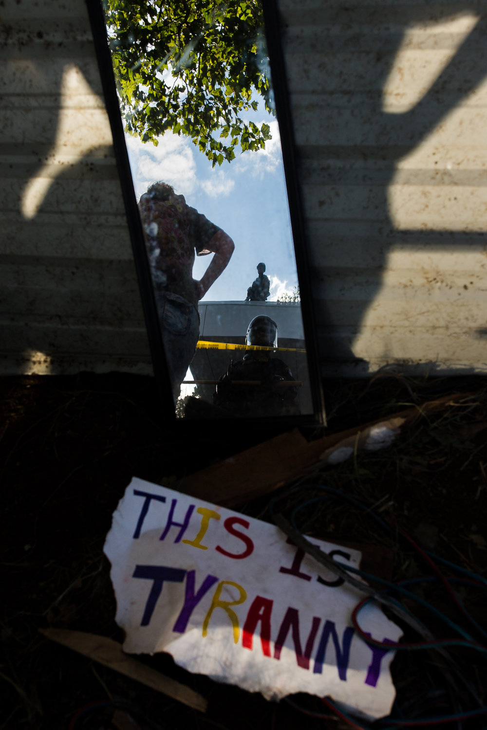 Portland police and Federal ICE agents are reflected during the Occupy ICE protest in Portland, Oregon, on June 28, 2018.