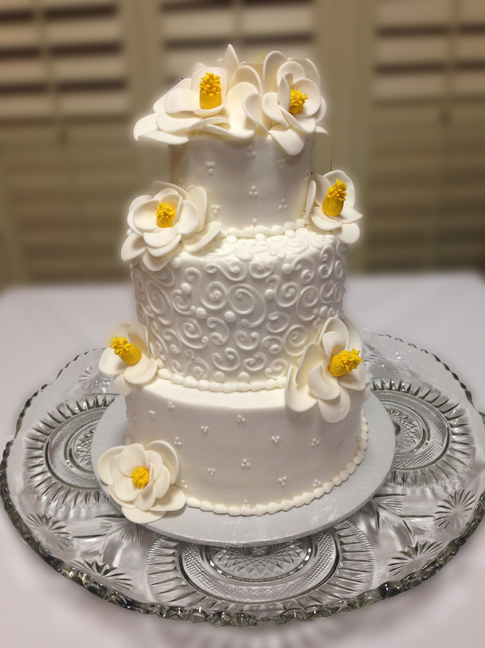 White, 3-tier cake with yellow floral accents