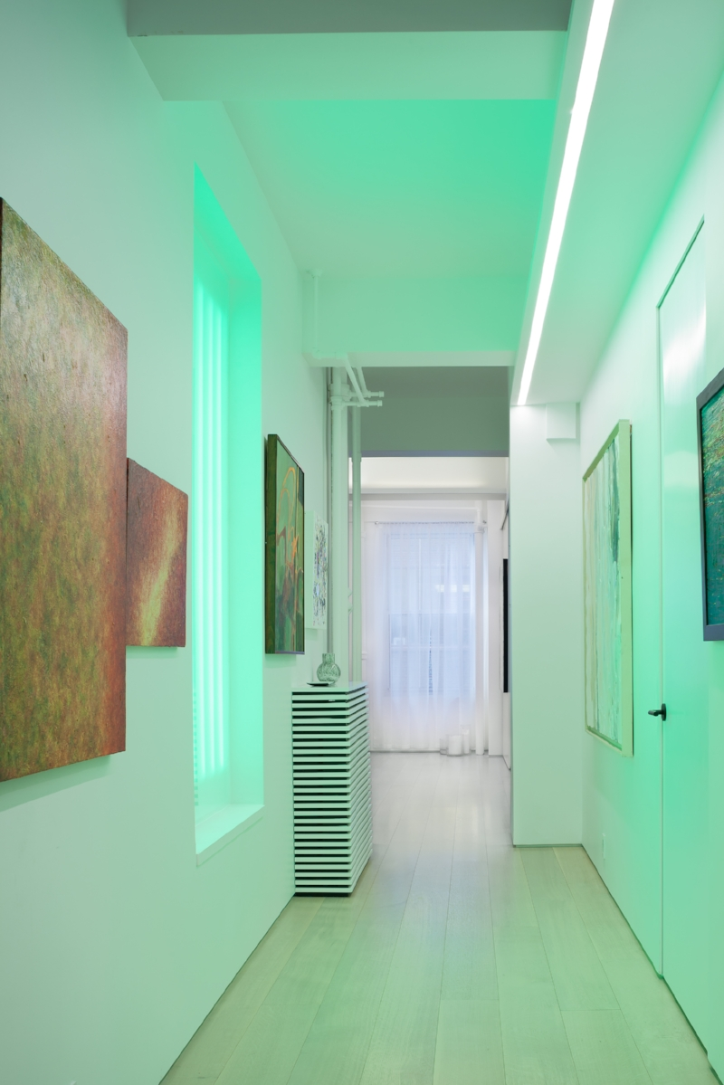 After - Clean and elemental. The same hallway with sleek lighting that gives an ambient glow. The drop ceiling was removed to expose the full ceiling. A trimless door and shadow reveal at the wall base remove unnecessary visual noise. The linear design of the radiator cover emphasizes the clarity and movement of the space. Wide plank clear wood flooring ties it all together. The same artwork now pops on the walls and can be really SEEN in a new light.