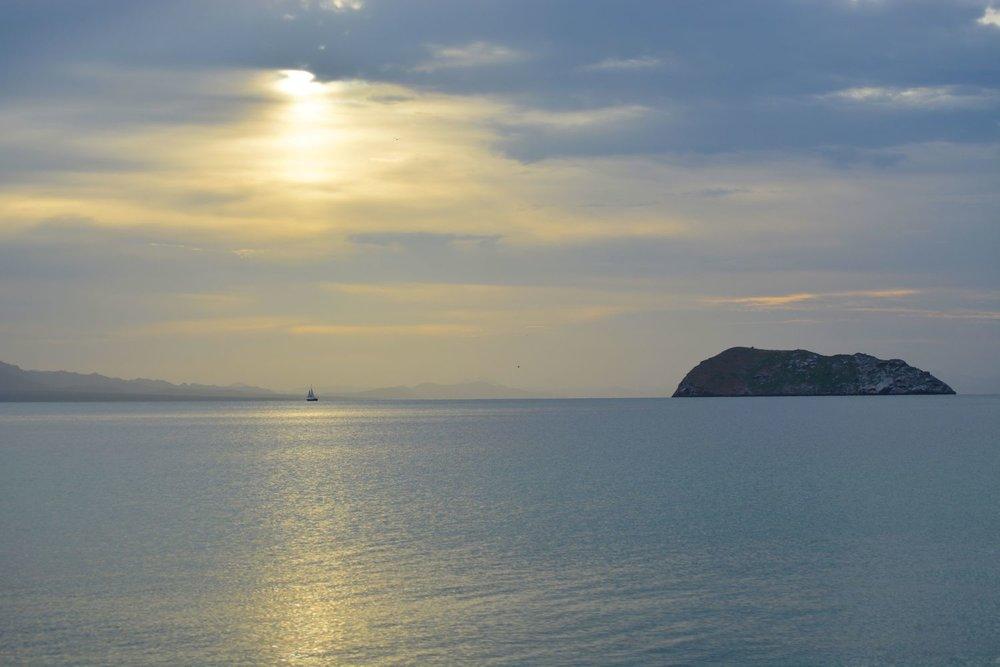 A sailboat passes by at sunrise.
