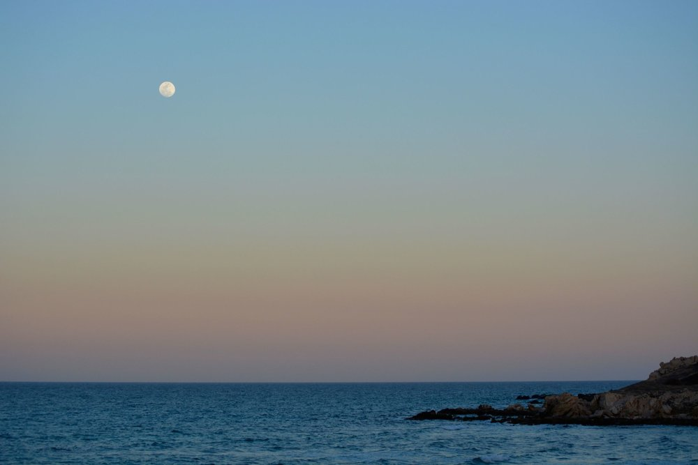 The moon rises over a gradient sunset in Los Arbolitos.