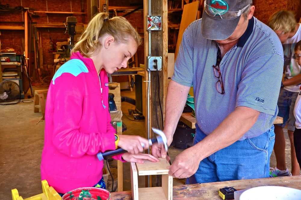 tessa-hammers-a-nail-into-her-project-while-mark-holds-the-boards-steady.jpg
