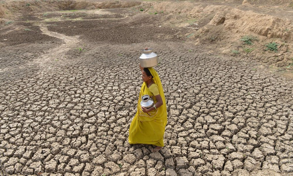 A woman walking across dry parched agricultural land caused by extreme drought in India.    Photo courtesy:   Sam Panthaky /AFP/Getty Images