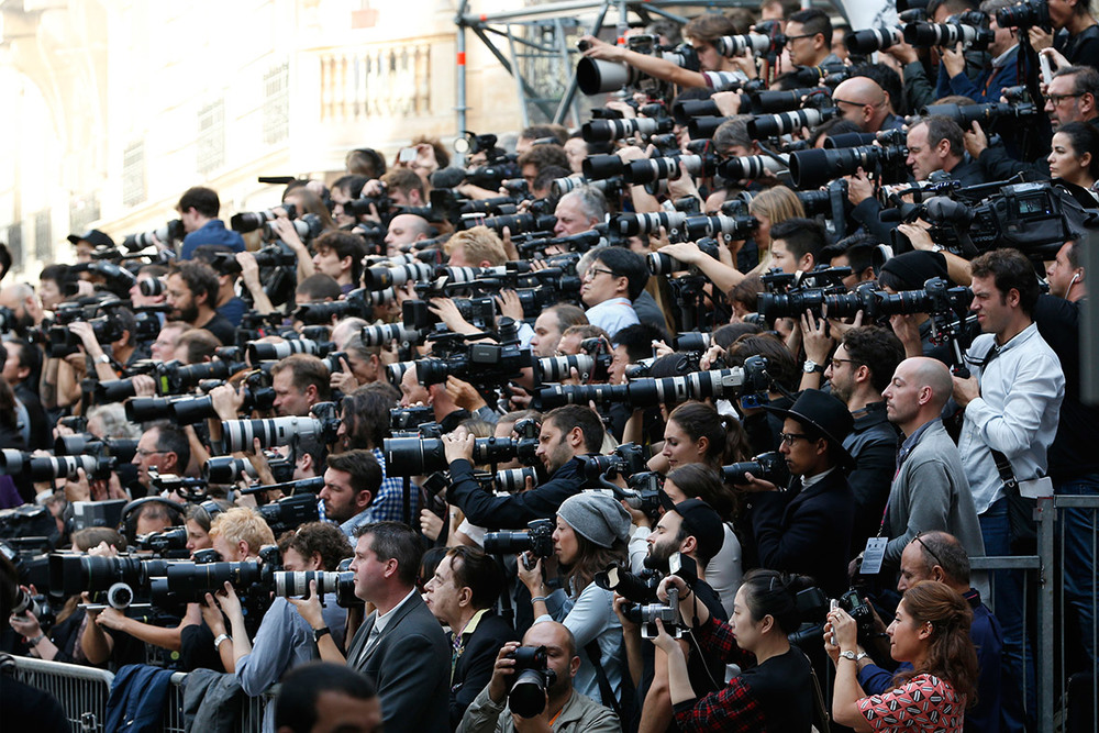 Photographers capturing and contributing to Fashion Week madness; image via
