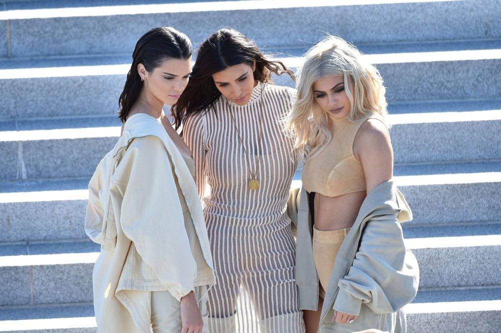 Kendall and Kylie Jenner with sister, Kim Kardashian at the Yeezy Season 4 show; image  via