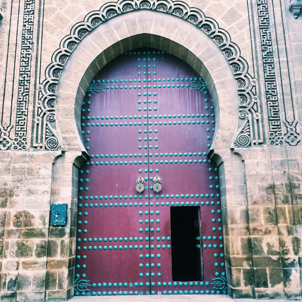 The horseshoe arch shape is common in Islamic architecture as seen here in the Quartier Habous near the palace.