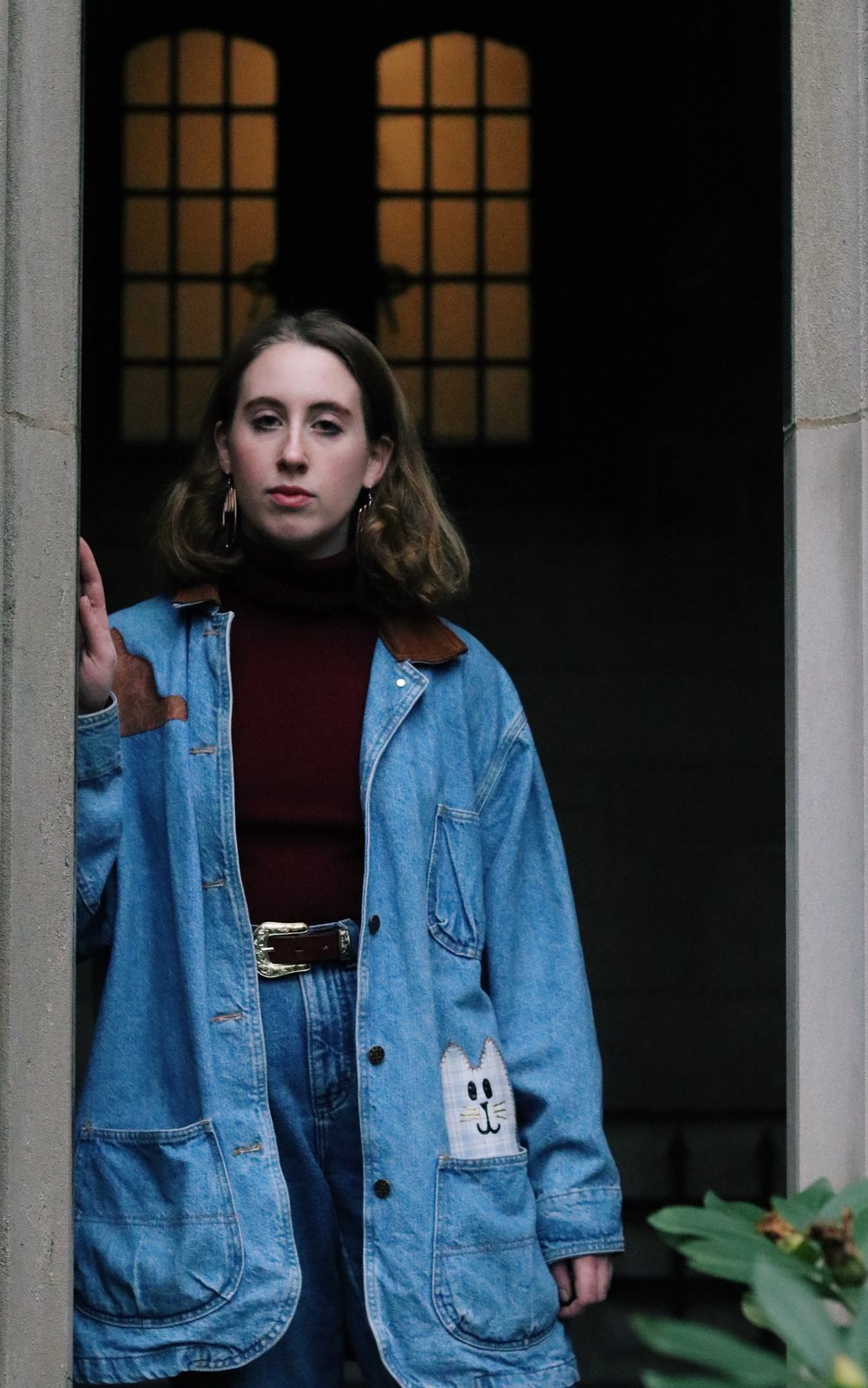 Jillian is wearing a thrifted turtleneck, belt and denim jacket, and vintage jeans from Etsy.
