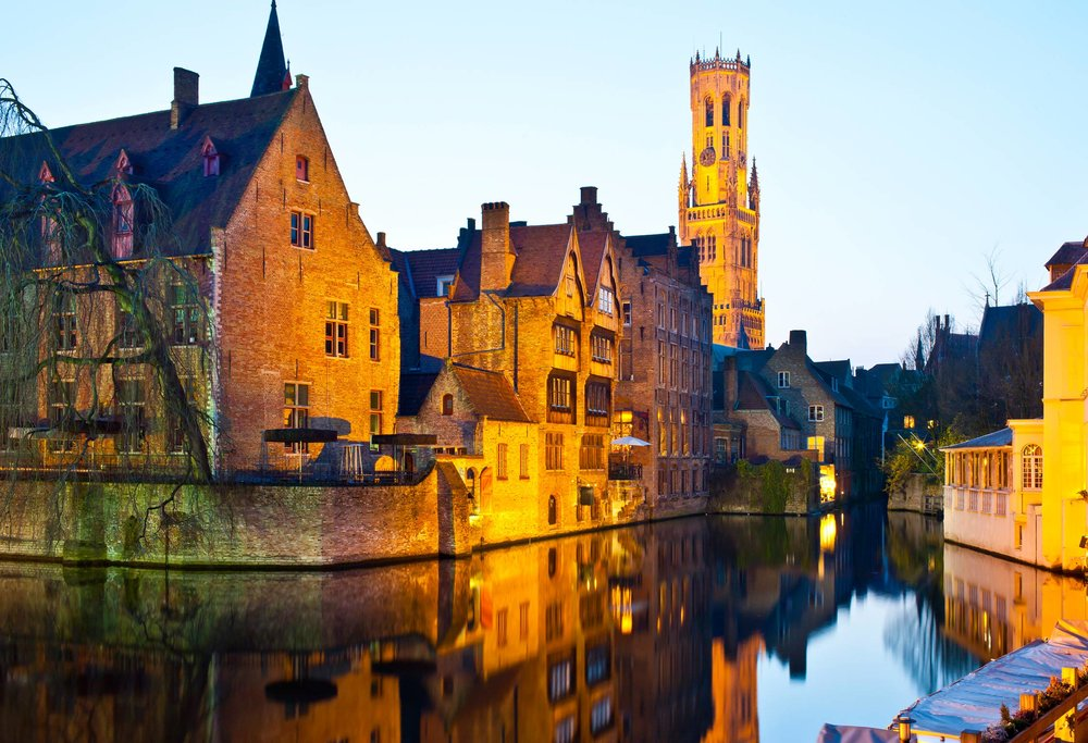 One of Bruges winding canals at sundown; image via