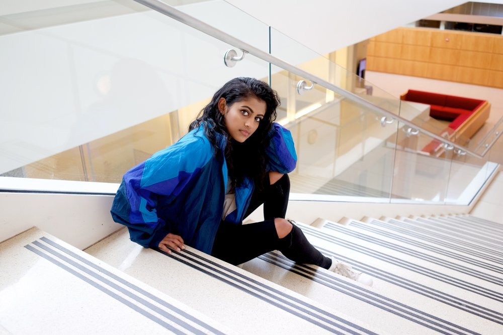 Here Yamini wears: a Reebok Jacket thrifted from Ragstock, a grey top from Nordstrom, jeans from Topshop, Adidas Stan Smiths, and a belt from Brandy Melville.