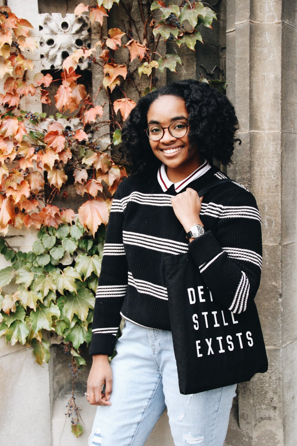 """Sweater: Gap, Collared Shirt: Von Maur, Jeans: Gap, Shoes: UGG,""""Detroit Still Exists"""" Tote:A Detroit local brand, Definitive Style Exclusive (check them out, they have awesome stuff made right in Detroit), Watch: Shinola (also amazing and made in Detroit)"""