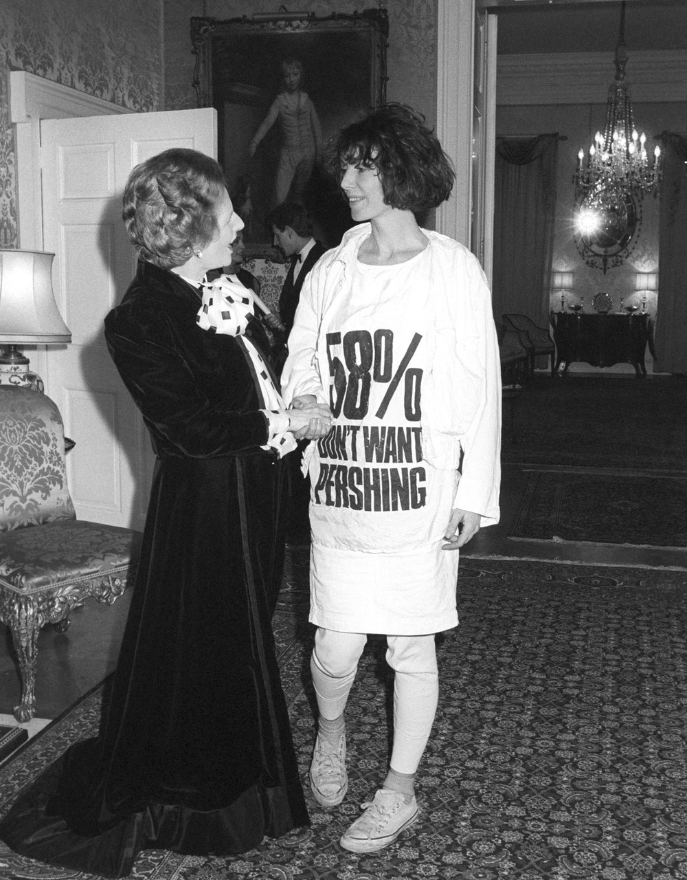 Hamnett meeting then Prime Minister Margaret Thatcher, wearing a t-shirt underlining a lack of public support for US Pershing missiles being stationed in the UK | Image  Via