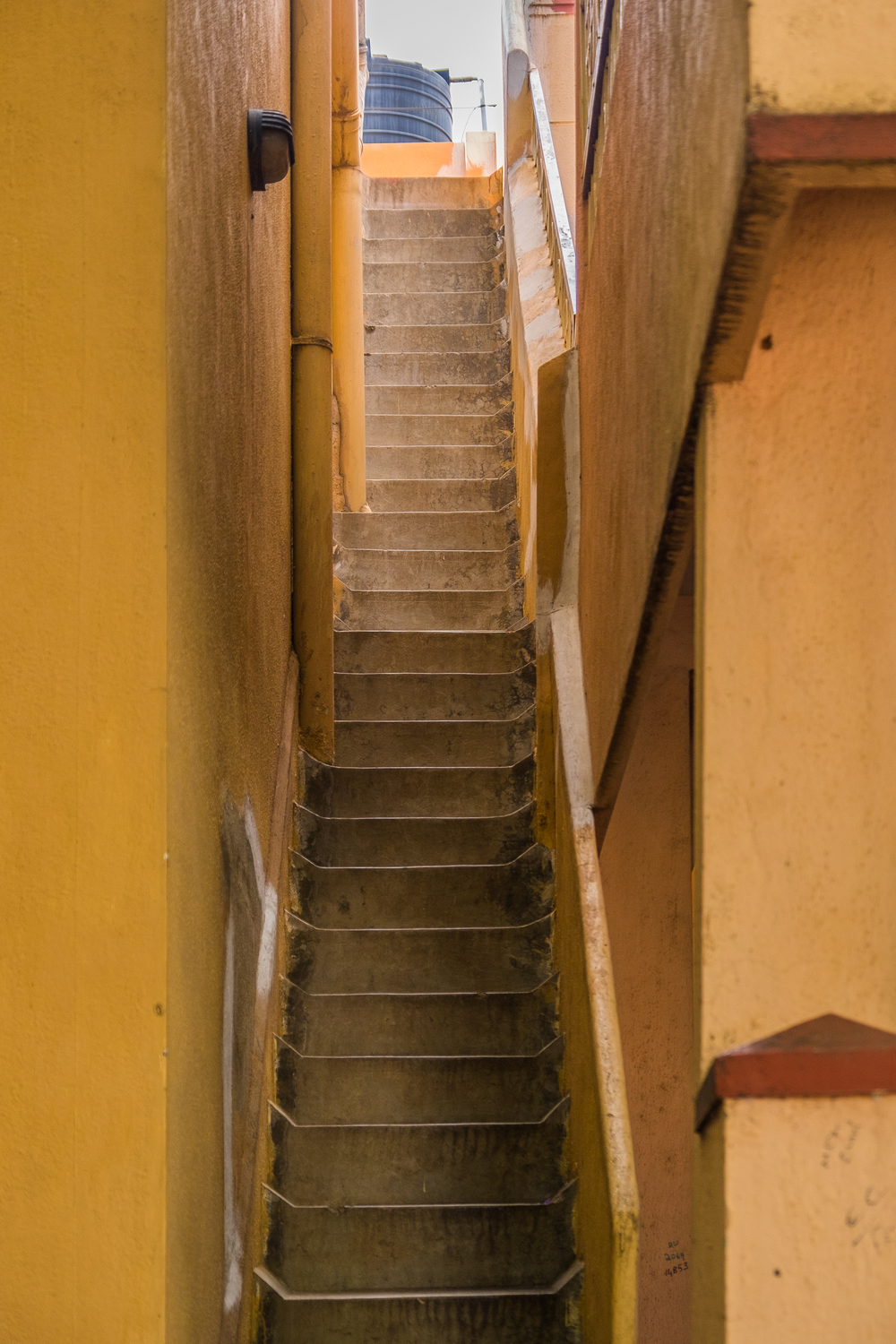 narrow alleyway staircase against yellow walls