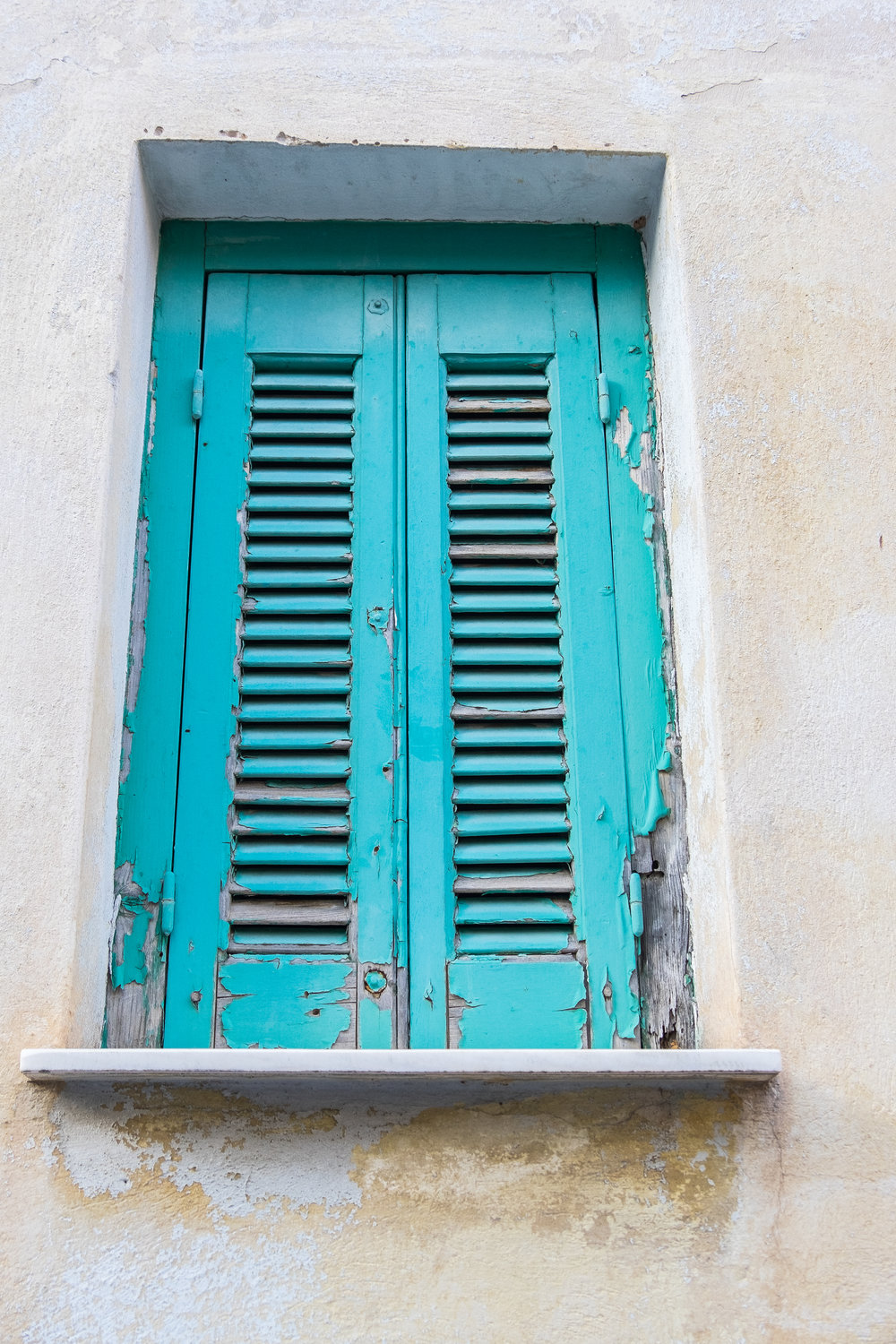 bright blue teal shuttered window with small window ledge