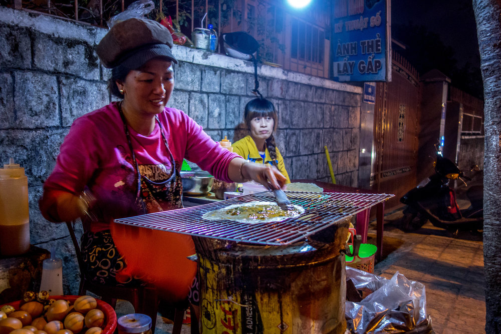 A woman making  banh trang nuong  on the street in Da Lat.