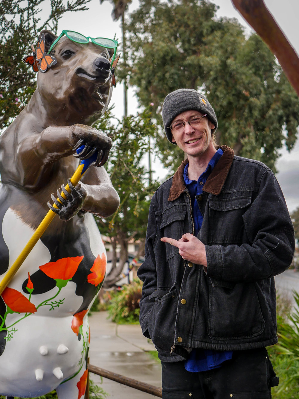 """""""Udderly Osos"""" a half-bear half-cow statue paddle boarding the sidewalk."""