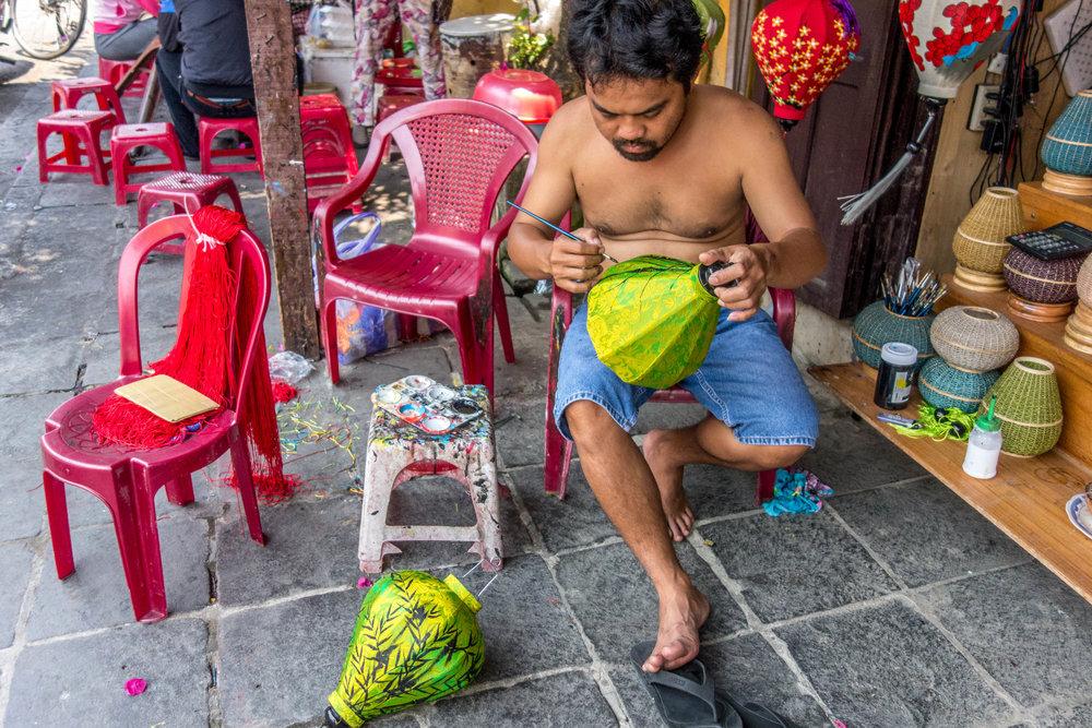 Man painting lanterns in Hoi An, Vietnam