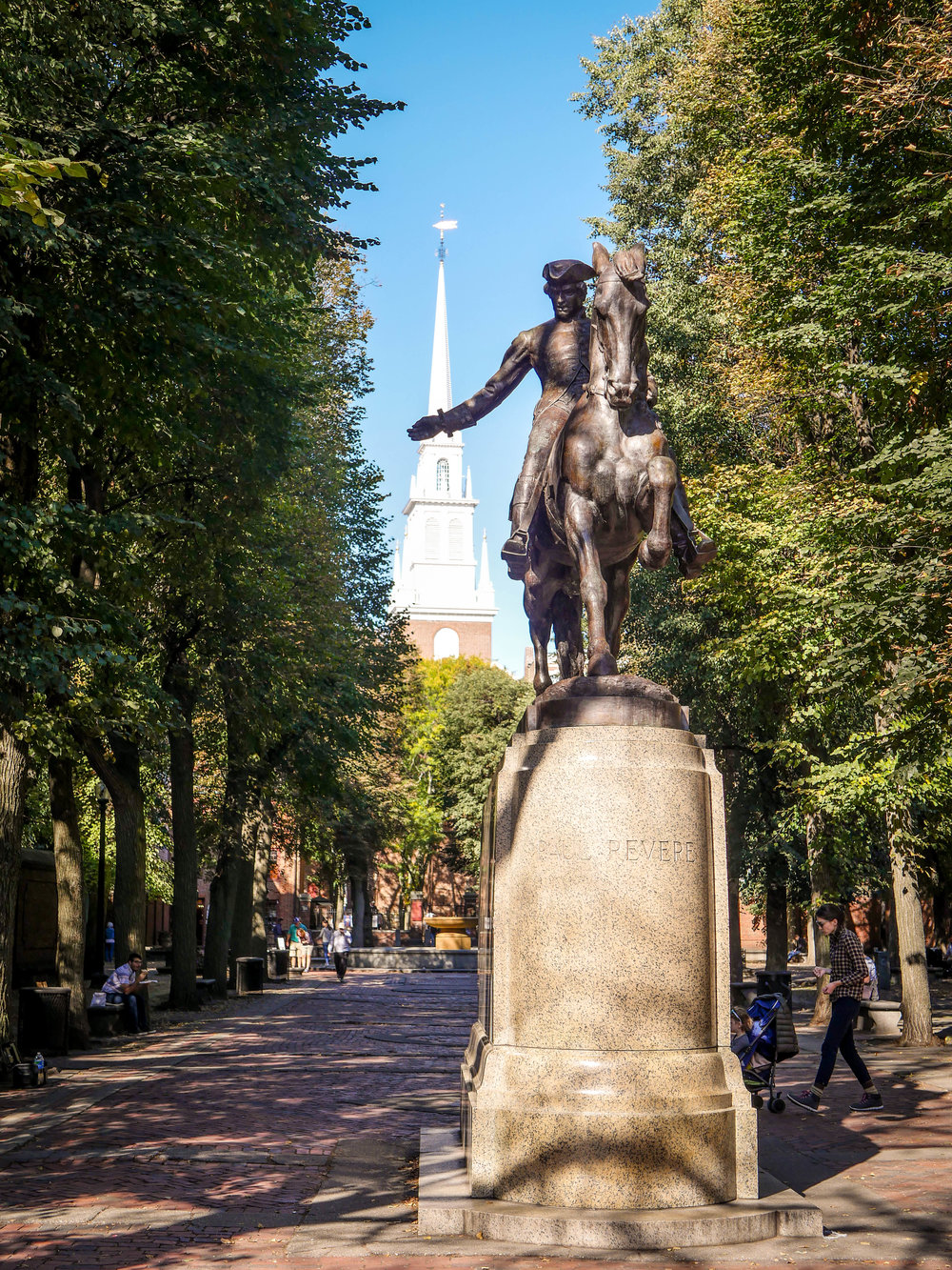 A statue of Paul Revere with Old North Church in the background.
