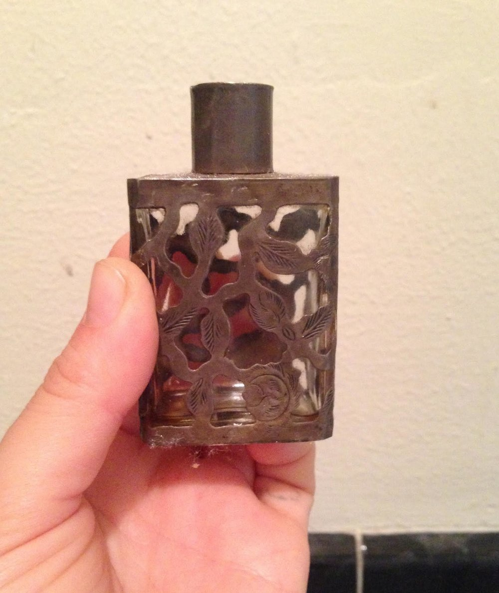 an old silver and glass perfume bottle with just a little oil left in the bottom