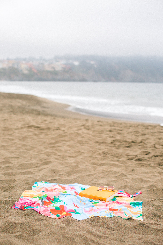 San Francisco Baker Beach Lifestyle Photoshoot. Beach reading, while showcasing colorful scarfs with Bridgette Thornton.