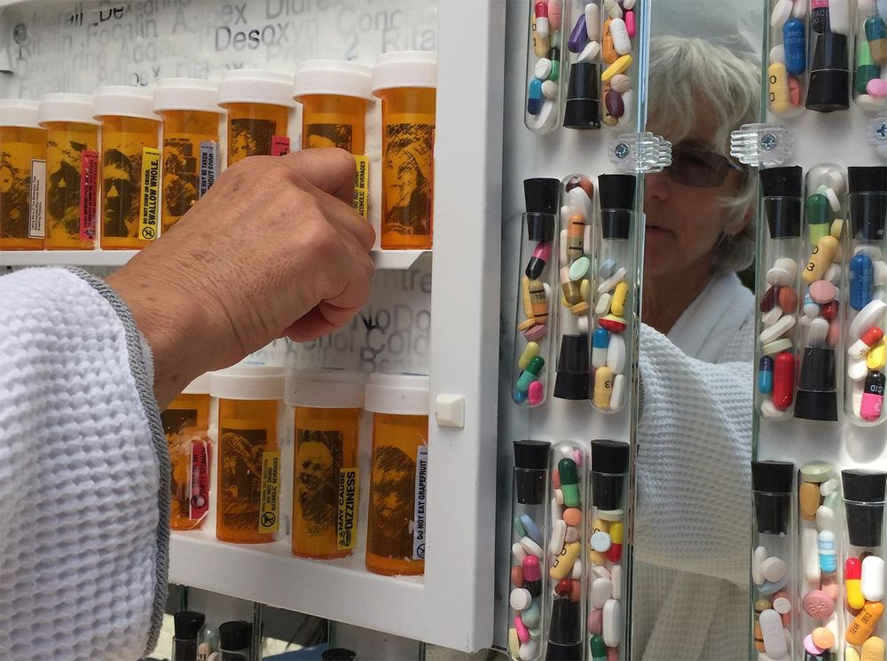 Mirror reflects person reaching into medicine cabinet. Prescription pill bottles with faces of captured users.