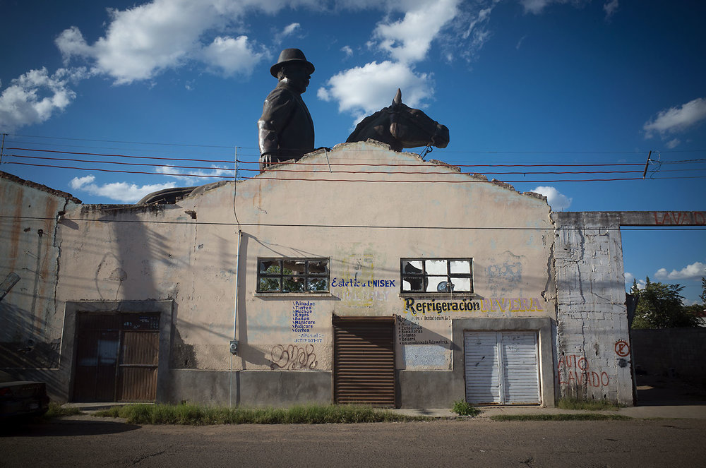 "An enormous statue of Francisco ""Pancho"" Villa sits behind the wall of an abandoned building in Hidalgo del Parral.  The city has a special affection for the famed revolutionary, who spent his later years near the city and was assassinated in its streets in 1923.  Parral boasts a museum dedicated to Villa as well as an annual reenactment of his death."
