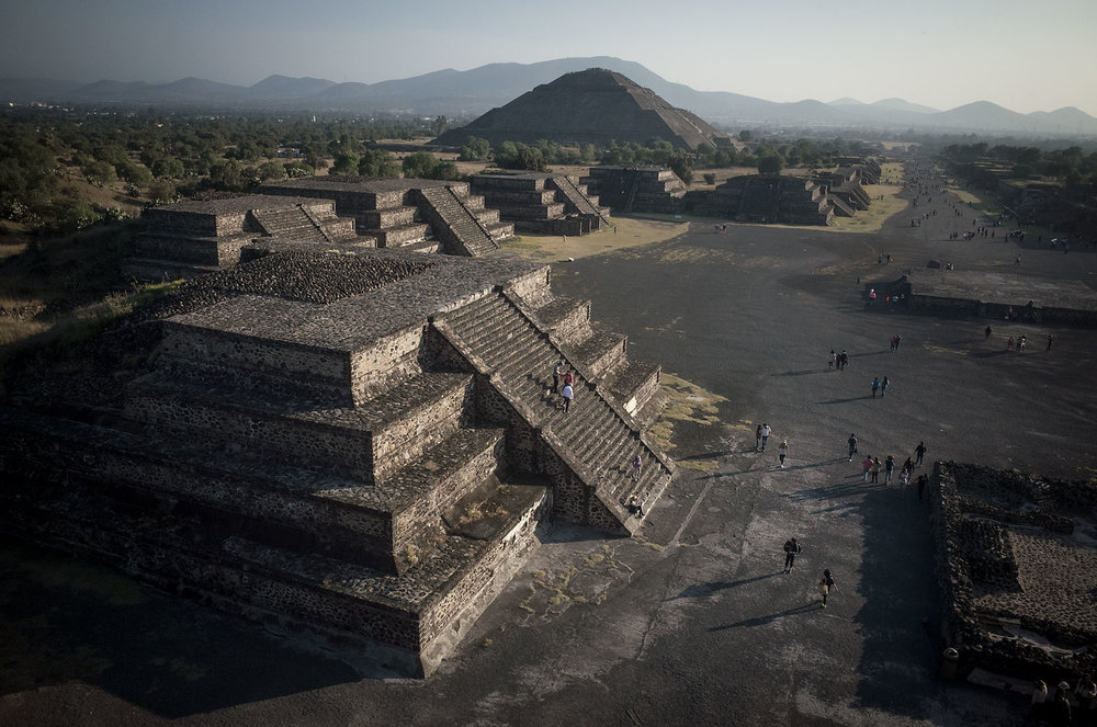 Visitors descend one of the zyggurat structures in Teotihuacan.  In the background is the Pyramid of the Sun.  Teotihuacan was once the largest city in Mesoamerica before its fall in 550CE.
