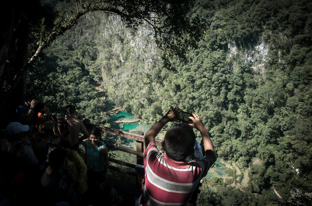 A child reaches over the crowds to take a picture of the natural pools at Semuc Champey.