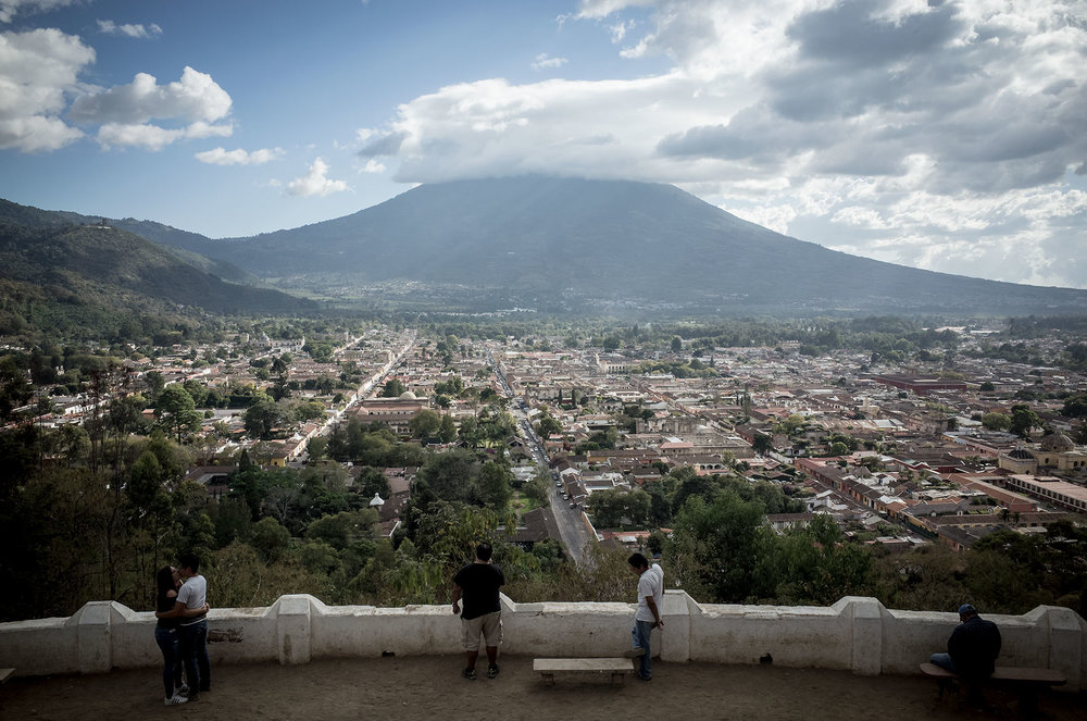 Visitors look out over the city of Antigua from a viewpoint atop Cerro de la Cruz, with the impressive Volcán de Agua rising up in the background.