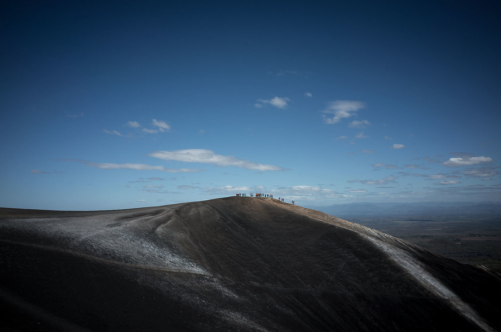 People atop Cerro Negro look down into one of the active craters.  The volcano, outside of León, Nicaragua, is the youngest in Central America.