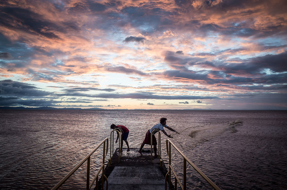 Teens cast fishing nets at sunset on Lake Nicaragua.