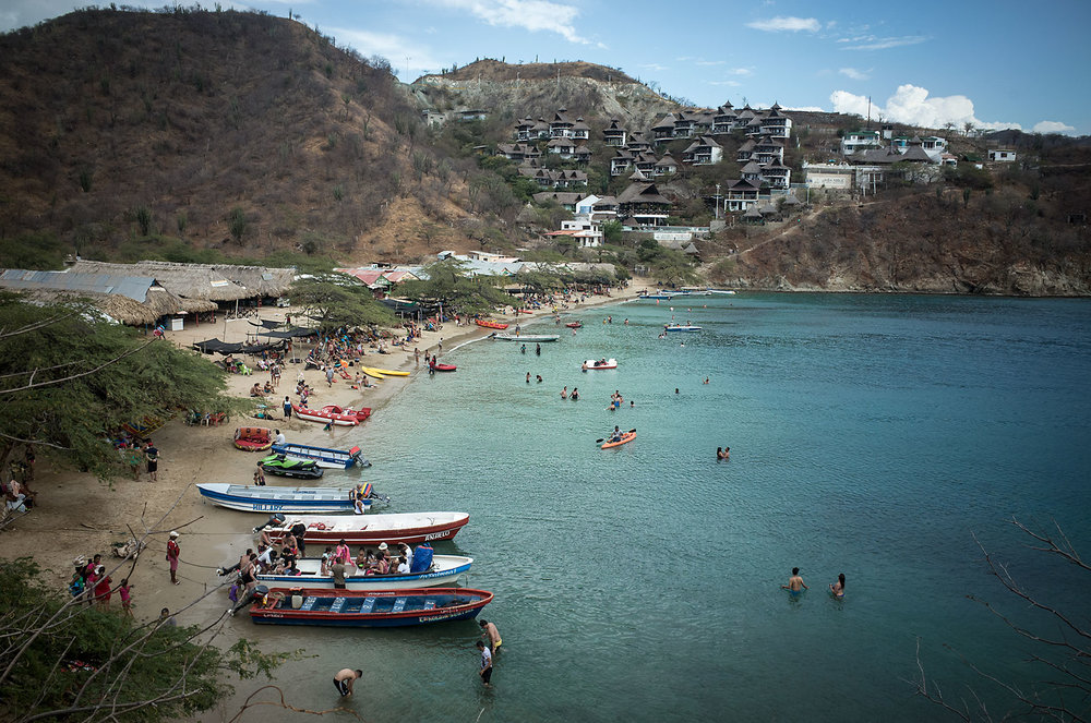 Boats and cabanas cradle the blue waters of Playa Grande, Colombia.