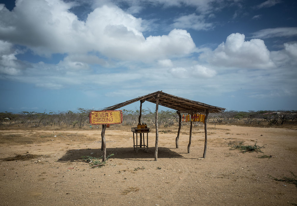A local gas vendor in the desert coast of La Guajira. Gas stations are rare past Uribia, so fuel tank calculations are important when leaving the asphalt. Luckily, locals repurpose plastic bottles as fuel containers,which they sell to desperate motorists.