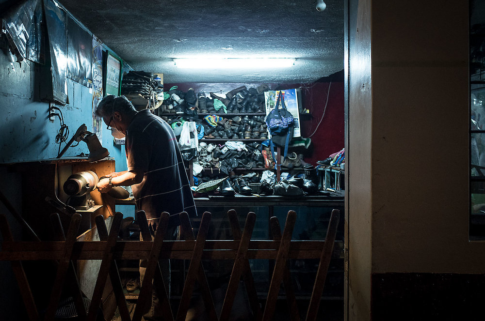 A shopkeeper repairs shoes late in the evening in Baños, Ecuador.