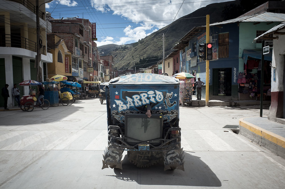 An arm reaches through the window to stabilize a television on the back of a mototaxi in La Unión, Peru.