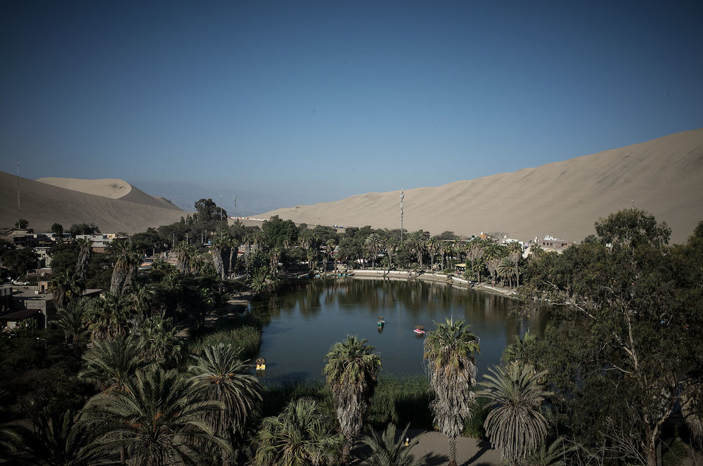 Huacachina is a literal oasis in the desert just outside of the southern Peruvian city of Ica.  Huge sand dunes, some several hundreds of feet tall, surround the small lagoon and its ring of palms.