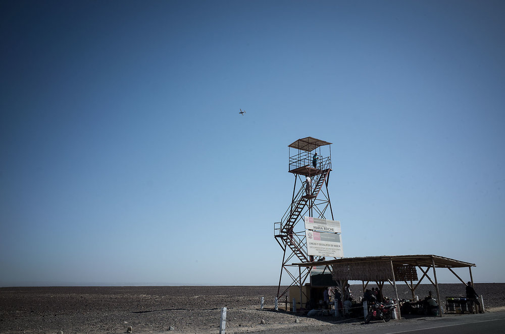 Visitors descend a lookout tower positioned to view the mysterious Nazca lines in southern Peru.  In the distance, one of the local airplane tours flies over the desert.