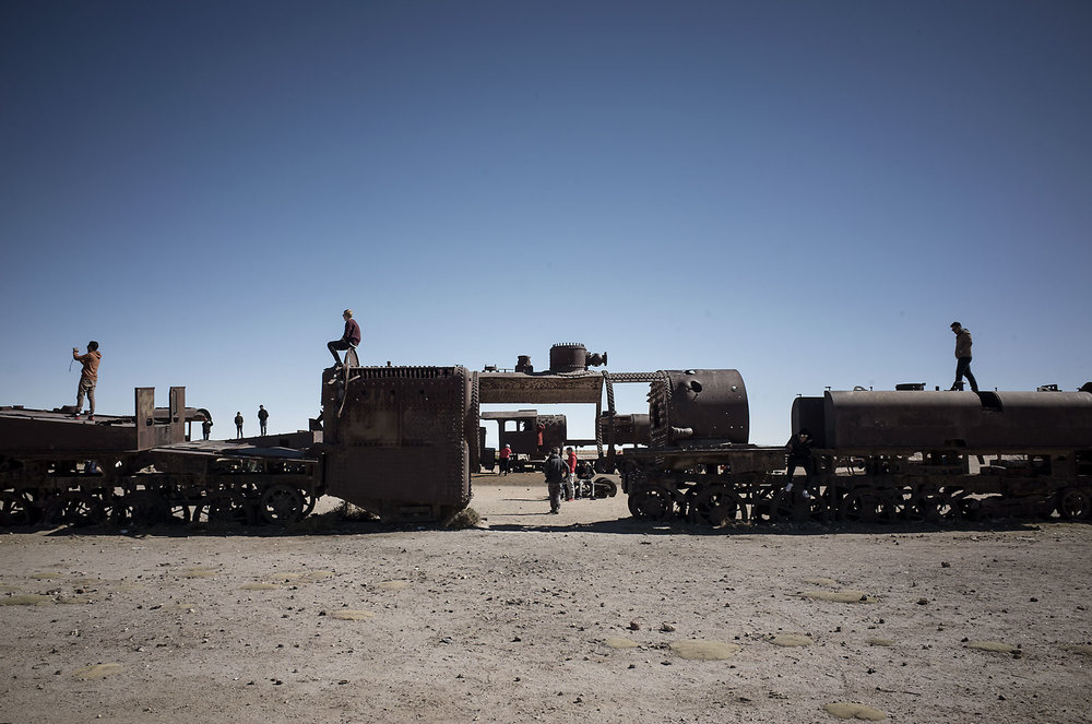 Visitors to Uyuni's train graveyard pose for photos atop locomotive carcasses.