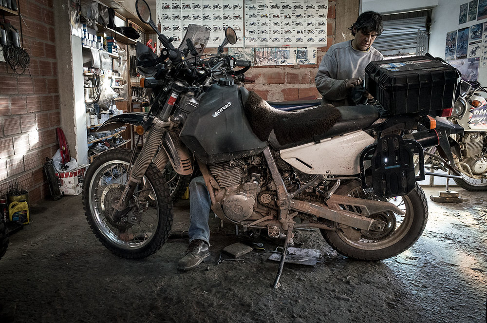 Two brothers repair the starter on a bike at their shop in Sucre, Bolivia.