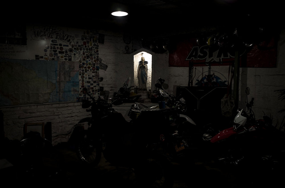 A statue of the Virgin watches vigil over motorcycles parked at a hostal in Santiago.