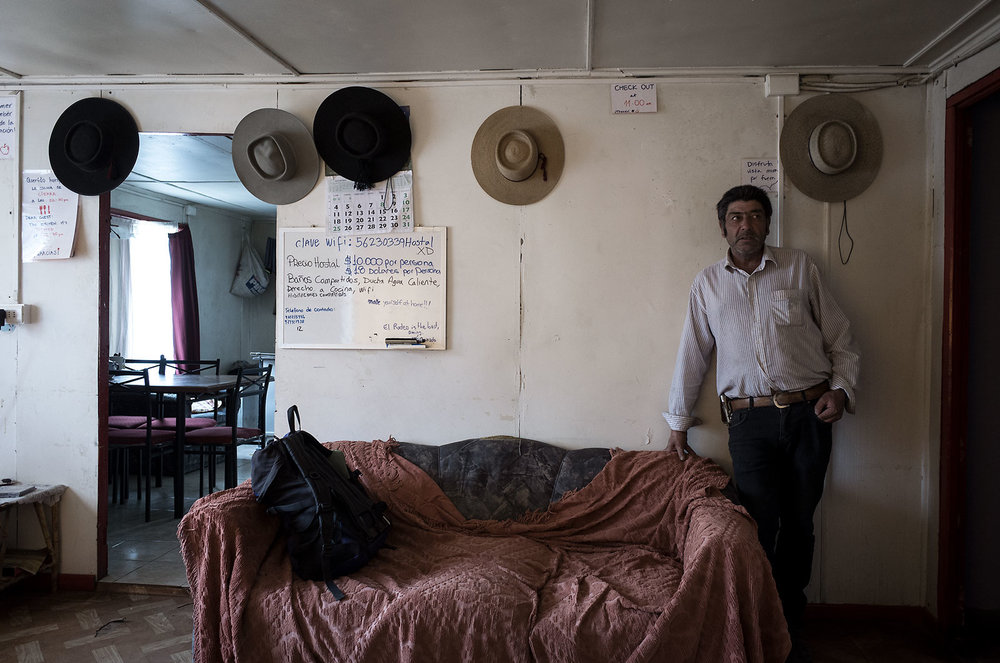 "Juan runs a hostel in Villa Cerro Castillo but has spent much of his life working with sheep.  He has consulted and trained others in the art of raising sheep, including various stints in the United States (""I liked Wyoming the most because it reminds me of Cerro Castillo"").  Here he poses with his various shepherd hats, which decorate the walls of the hostel."