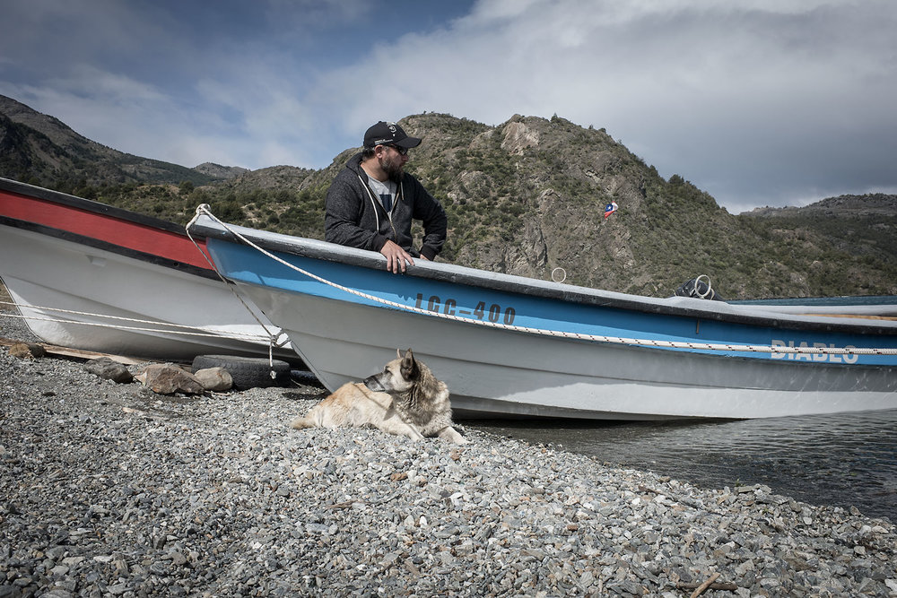 Jose and his three-legged dog Anska, wait for the wind to die down on Lake General Carretera.  Jose offers boat tours of the marble caves near Puerto Sanchez.
