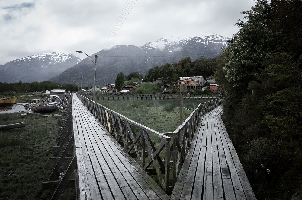 An intersection of boardwalks in Caleta Tortel, Chile, a town built on the hillsides surrounding an inlet in the Baker Channel.  Due to the lack of flat space homes in Tortel are built on stilts.  A system of wooden boardwalks allow people to navigate the village, as there are no roads.