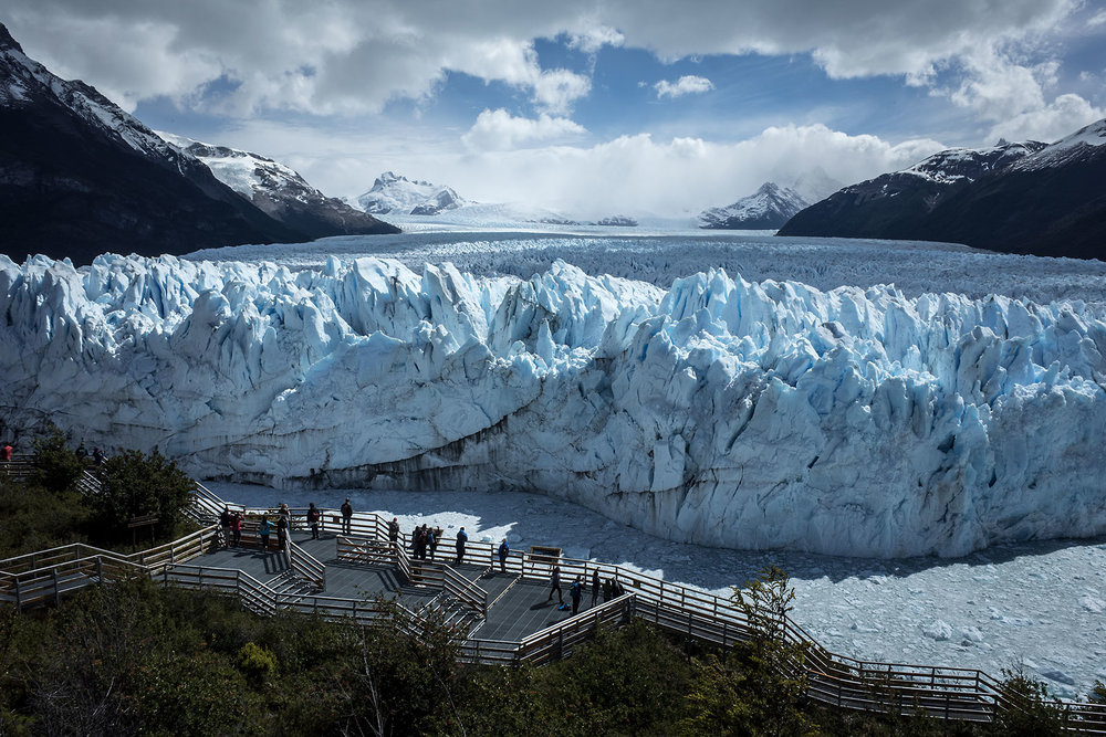 Vistors observe the Perito Moreno glacier from a viewing platform in Los Glaciares National Park, Argentina.  The terminus of the glacier is 5km wide and towers 70m above the water level.  It is one of the only glaciers in the world that is advancing.