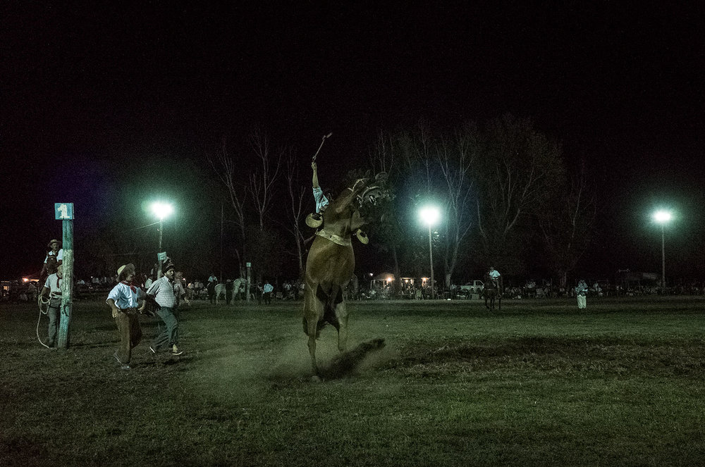 A gaucho tries to stay on a bucking horse at the annual rodeo in Venticinco de Mayo, Argentina.