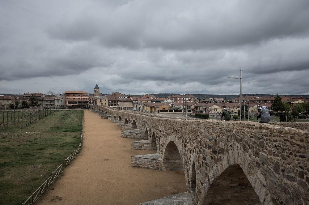 Pilgrims crossing the bridge into Hospital de Órbigo.