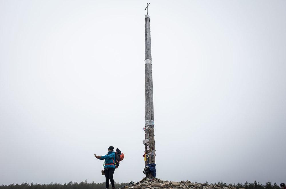 A pilgrim takes a selfie in front of the Cruz del Hierro.